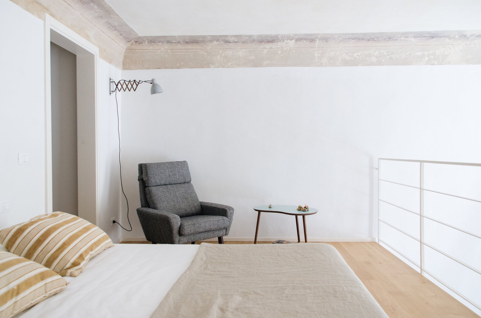 Bedroom, Bed, Chair, Wall Lighting, Light Hardwood Floor, and Night Stands Midcentury modern mixes well within the context of the 16th-century palazzo.  Photo 5 of 20 in A 16th-Century Florentine Palazzo Is Transformed Into an Artist Residency