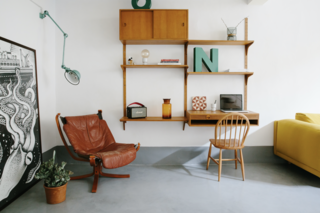 One of the spaces holds a midcentury, wall-mounted storage system and desk.