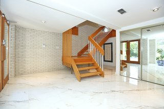 The entrance features marble floors and a grand staircase. The home was built with sturdy 2x6 construction and features plastered walls throughout.
