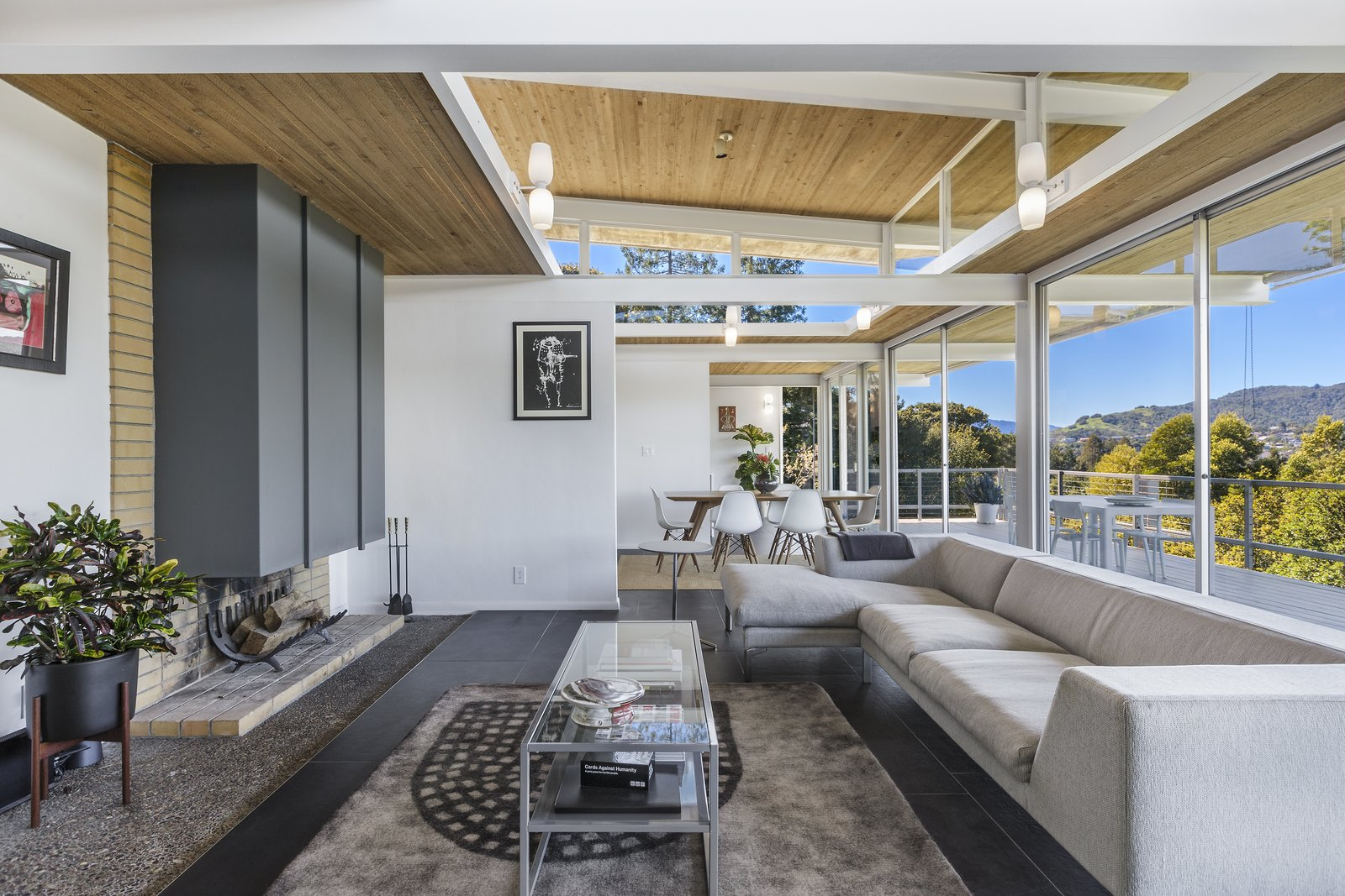 Living Room, Coffee Tables, Sectional, Wall Lighting, Rug Floor, Wood Burning Fireplace, Table, Chair, and Concrete Floor  Photo 6 of 17 in Spend the Night in an Iconic Case Study House North of San Francisco