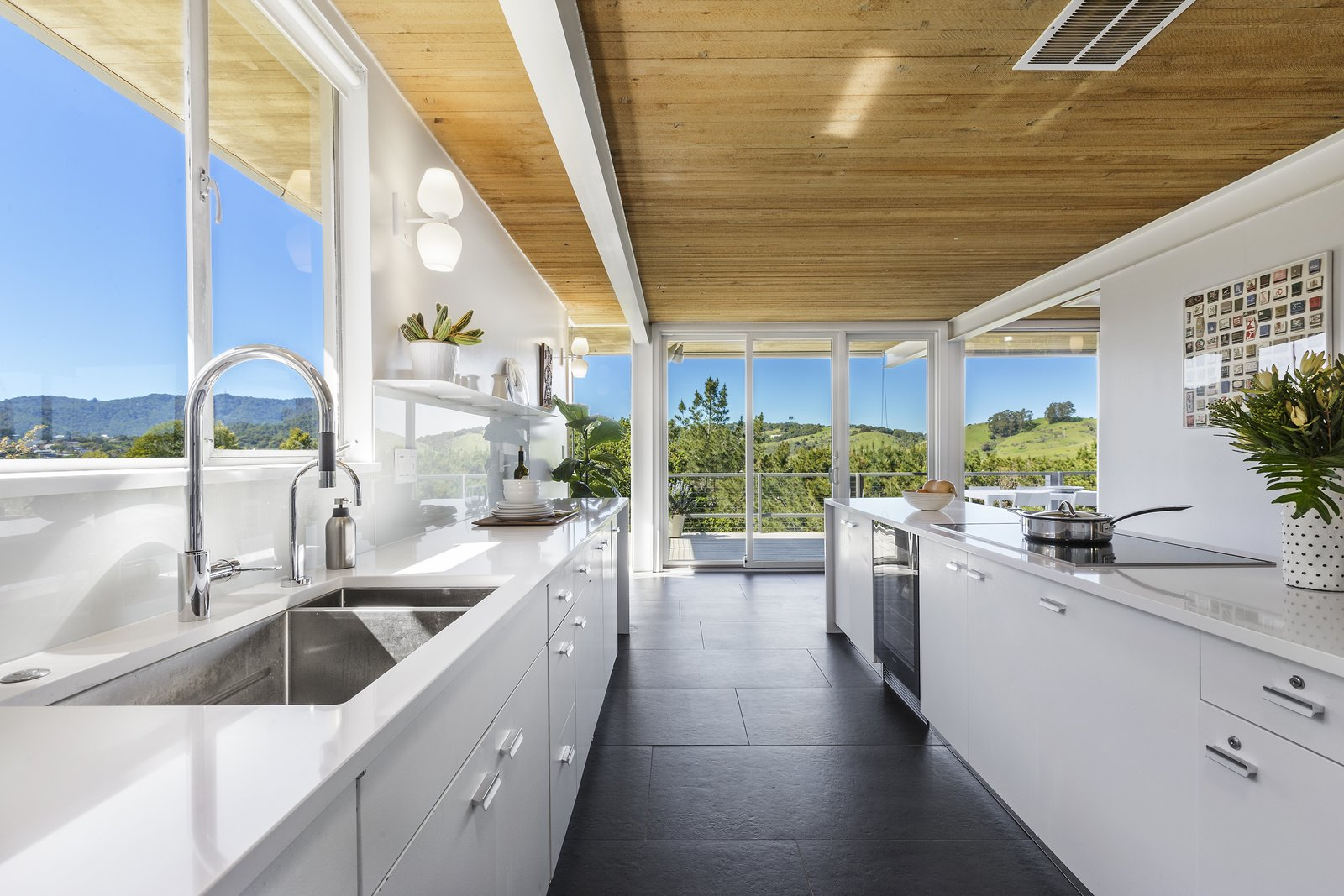 Kitchen, Wall Lighting, White Cabinet, Open Cabinet, Cooktops, Undermount Sink, and Beverage Center  Photo 13 of 17 in Spend the Night in an Iconic Case Study House North of San Francisco