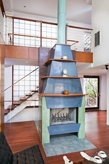 A fireplace assembled with three different colors on its concrete panels is the centerpiece of the spacious living area.