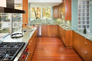 The kitchen features high-end appliances and cabinets elegantly paired with green marble countertops and tiling.
