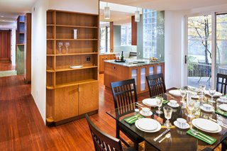 The kitchen opens to the dining room area which features a balcony overlooking the surrounding woods.