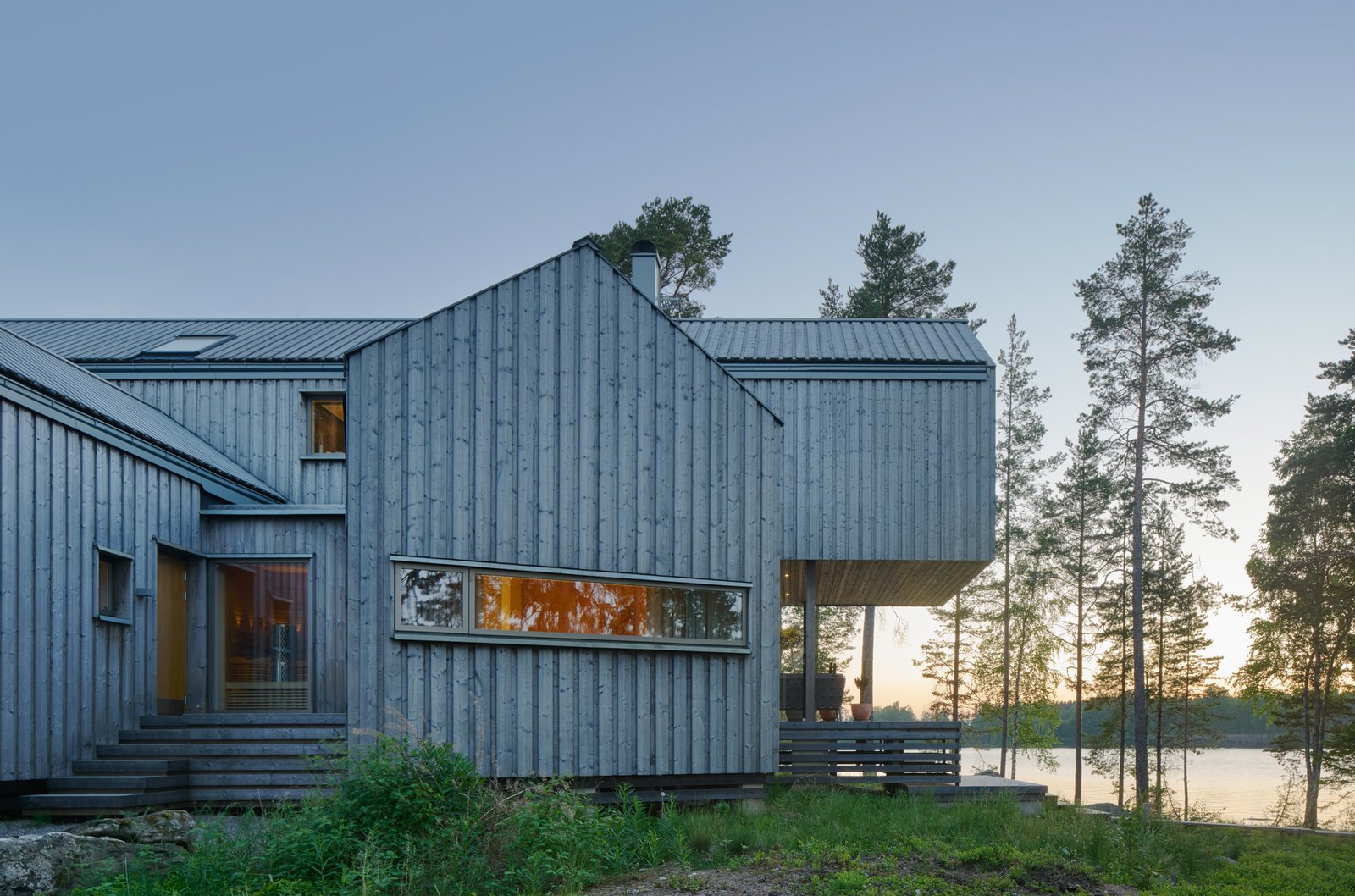 Exterior, Gable, Glass, Cabin, House, Wood, and Metal  Best Exterior Metal Wood House Glass Cabin Photos from A Swedish Family's Dreamy Villa Fans Out For Lakeside Views