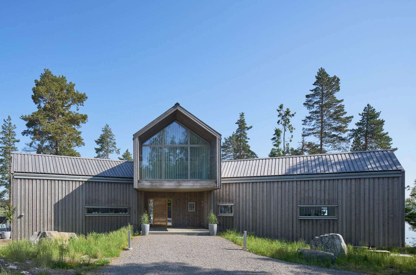 Exterior, Cabin Building Type, House Building Type, Glass Siding Material, Gable RoofLine, Metal Roof Material, and Wood Siding Material  Photo 9 of 21 in A Swedish Family's Dreamy Villa Fans Out For Lakeside Views