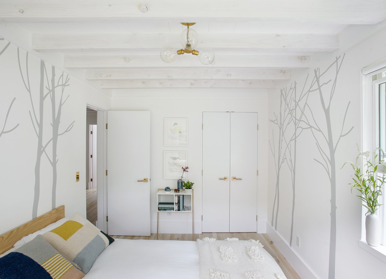 Bedroom, Bed, Light Hardwood Floor, Ceiling Lighting, Storage, and Wardrobe  Best Photos from A Hamptons Beach Retreat Gets a Scandinavian-Style Makeover