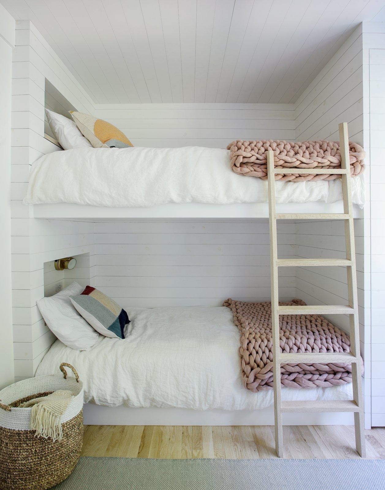 Bedroom, Light Hardwood, Rug, Wall, and Bunks  Best Bedroom Wall Rug Light Hardwood Photos from A Hamptons Beach Retreat Gets a Scandinavian-Style Makeover