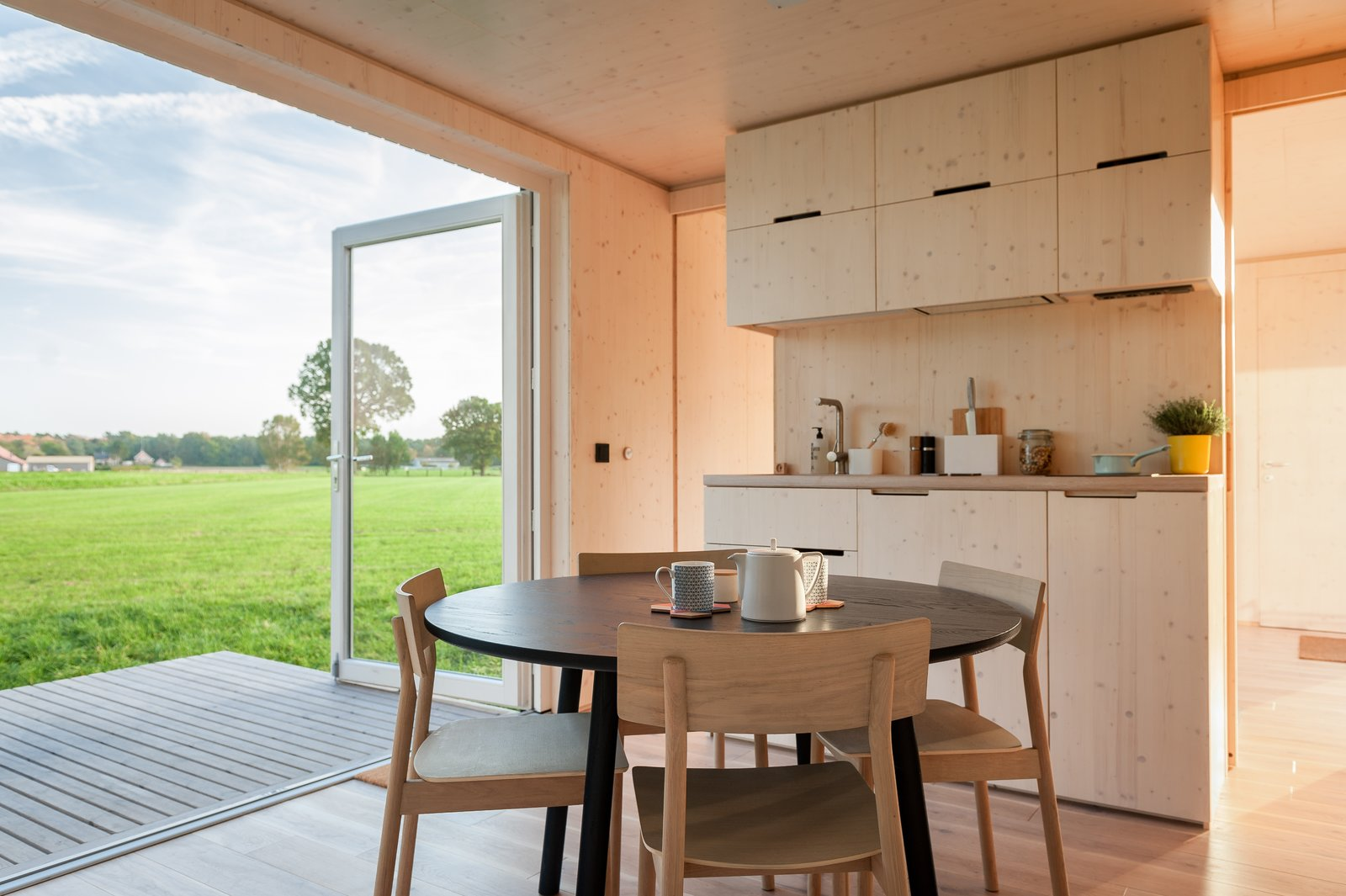 Dining Room, Light Hardwood Floor, Chair, Table, and Storage  Photo 7 of 12 in These Off-the-Grid Cabins in Belgium Keep Their Locations Secret Until You Book
