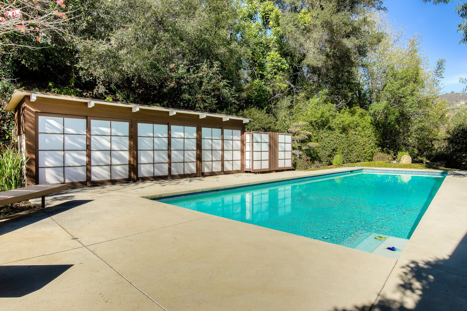 Outdoor, Back Yard, Large Pools, Tubs, Shower, Swimming Pools, Tubs, Shower, Trees, and Large Patio, Porch, Deck  Photo 7 of 10 in An Exceptional Midcentury by Case Study Architect Pierre Koenig Hits the Market