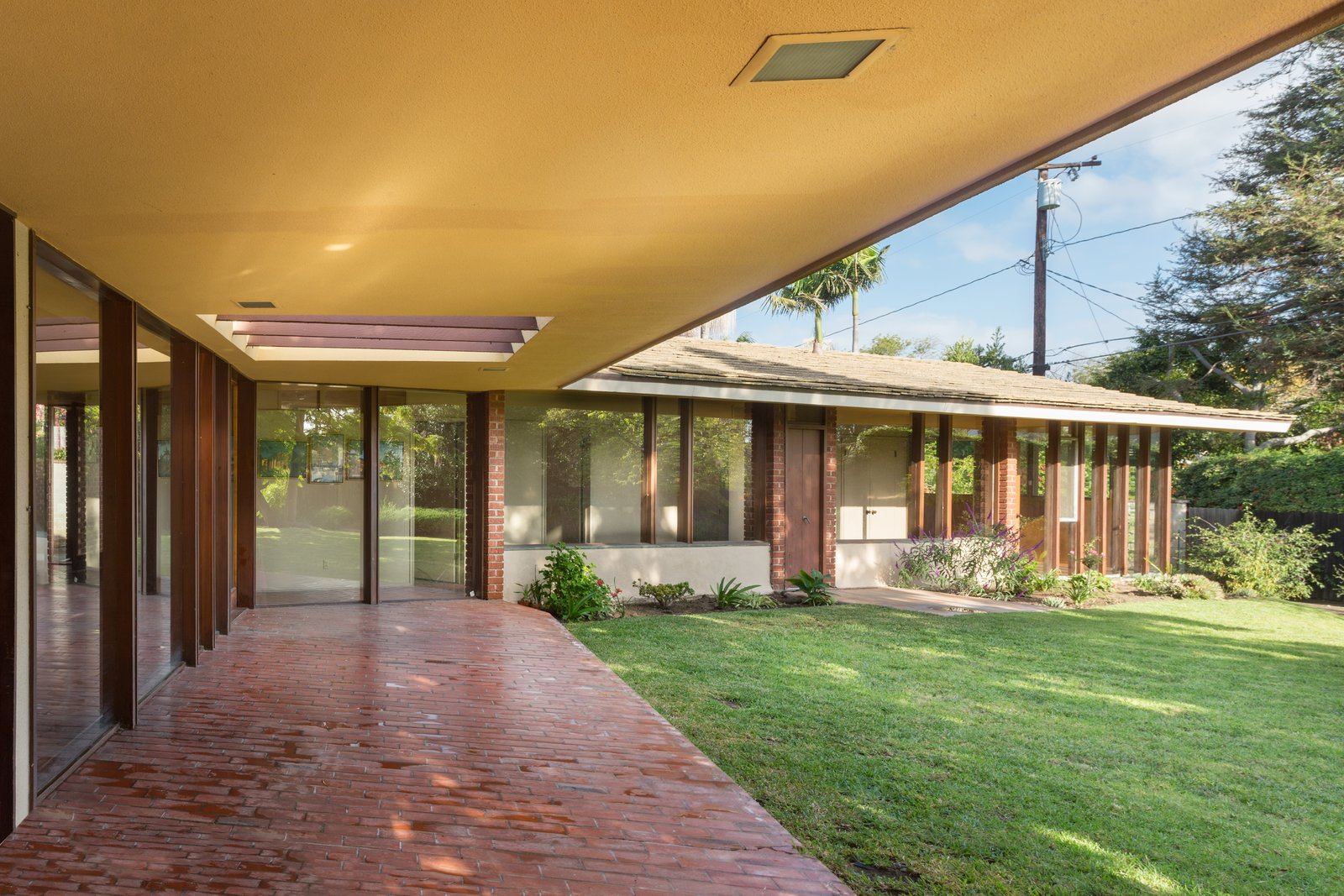 Outdoor, Back Yard, Stone Patio, Porch, Deck, and Grass  Photo 6 of 6 in A Pristine John Lautner Home in Long Beach Is Available For the First Time