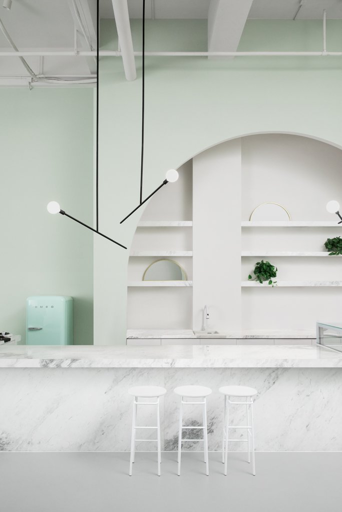 Kitchen, Marble Counter, Concrete Floor, Pendant Lighting, and White Cabinet  Best Photos from This Wes Anderson-Inspired Cafe in China Is Majorly Instagrammable