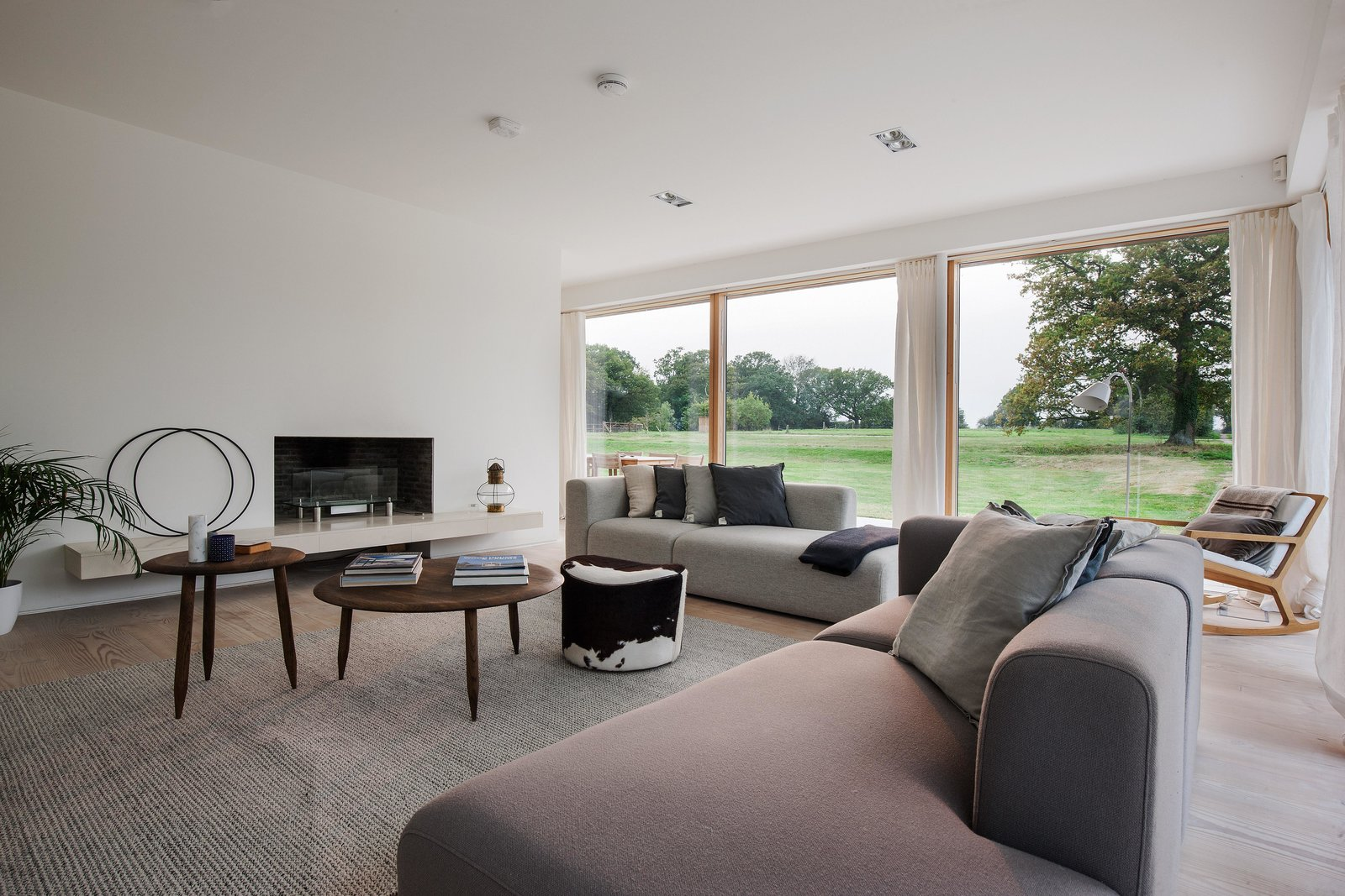 Living Room, Sectional, Coffee Tables, Light Hardwood Floor, Gas Burning Fireplace, Chair, Rug Floor, Recessed Lighting, Lamps, Floor Lighting, Ottomans, and Table Lighting  Photos from A Scandinavian-Style Pavilion in England Is Listed For $2.1M
