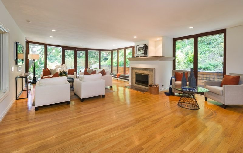 Living Room, Chair, Sofa, Standard Layout Fireplace, Medium Hardwood Floor, Lamps, Bench, Floor Lighting, Coffee Tables, and Recessed Lighting  Photo 9 of 16 in Anna Faris Lists Her Midcentury Abode in the Hollywood Hills For $2.5M