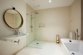 The minimalist bathroom design features an open shower and a freestanding tub.