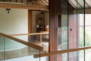 The converted barn home exhibits a striking juxtaposition of wood and glass.