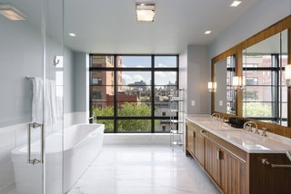 The luxurious master bath has a double vanity, soaking tub, glass-enclosed stall shower, and a wall of windows.