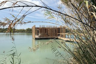 The architecture evokes a rustic construction in the midst of the lake's reeds.