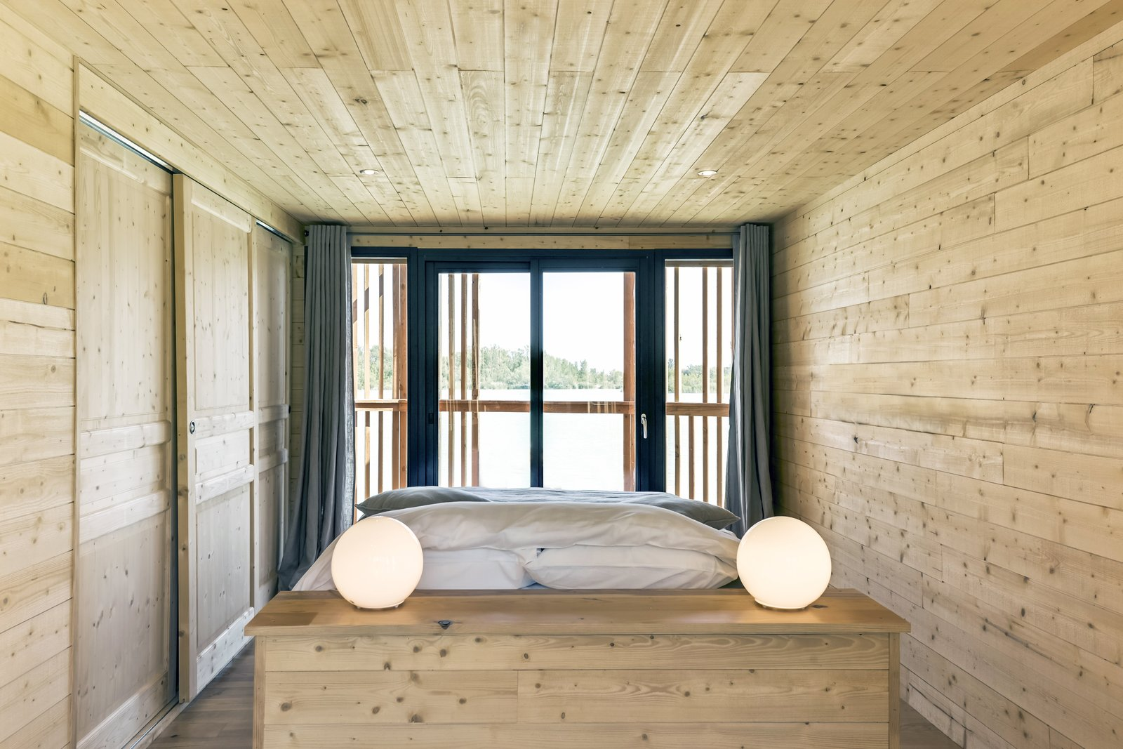 Bedroom, Table Lighting, Light Hardwood Floor, Bed, and Recessed Lighting The minimalist interiors of the suites.  Photo 9 of 13 in Drift Off in a Prefab Cabin at This Floating Hotel in France