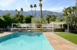 A Luminous Palm Springs Midcentury Asks $3.35M - Photo 12 of 16 - The outdoor entertaining space includes a shuffleboard court and a built-in outdoor seating area complete with a fireplace and barbecue.