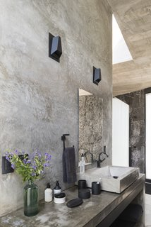 The raw materiality of the interiors is reflected in one of the bathrooms.
