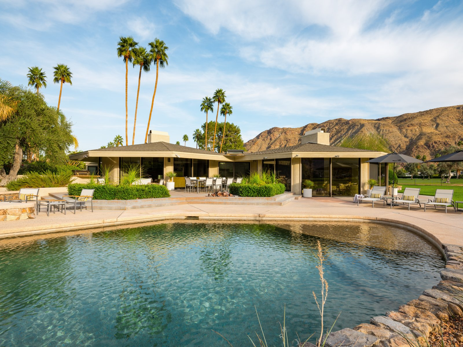 Outdoor, Shrubs, Large Patio, Porch, Deck, Trees, Back Yard, Desert, Swimming Pools, Tubs, Shower, and Grass T  Photo 16 of 19 in Own William Krisel's Palm Springs Pod House For $2.5M