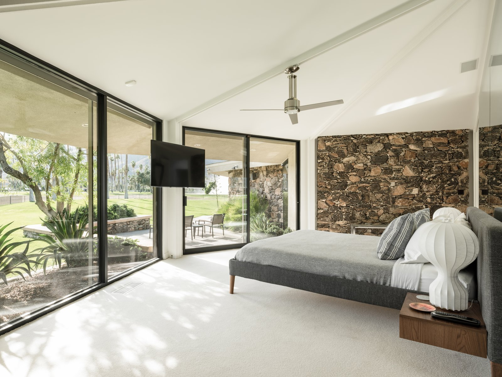 Bedroom, Ceiling Lighting, Lamps, Bed, Carpet Floor, Night Stands, and Table Lighting The master bedroom.  Photo 11 of 19 in Own William Krisel's Palm Springs Pod House For $2.5M