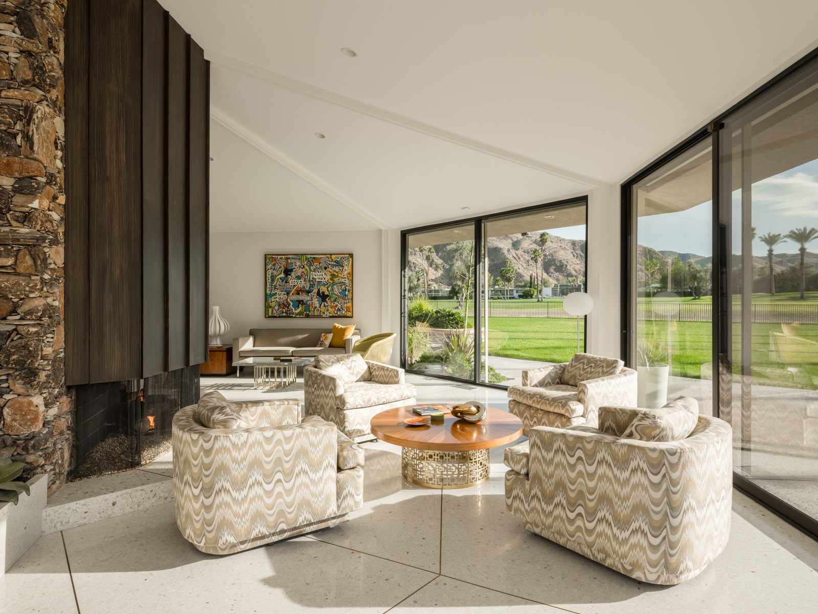 Living Room, Coffee Tables, Two-Sided Fireplace, Sofa, Chair, Terrazzo Floor, Floor Lighting, End Tables, Lamps, Recessed Lighting, and Table Lighting An alternate view of the living space and wood-paneled fireplace.  Photo 9 of 19 in Own William Krisel's Palm Springs Pod House For $2.5M