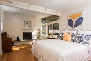 Along with the bright, airy setting, the master bedroom also features a fireplace.
