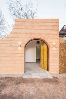 In the renovation of a traditional cave home in Weinan, China, the arched front entrance mimics the curve of the caves, and the wooden front door with contrasting black hinges swings open in two parts.