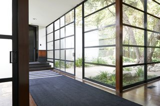 A steel-and-glass wall of windows surrounds the interior courtyard.