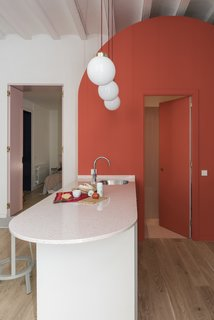 The rounded island houses a sink and dishwasher, and also doubles as an informal eating area.