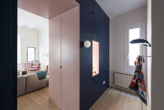 A cut-out pink doorway connects the living area to the entrance, while hiding the closet doors on both sides.