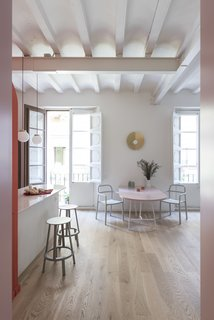 """Between the two big windows, the golden """"Fold Lamp"""" presides over the dining area, which consists of a wide pink lacquered table. The Ypperlig chairs pictured above are by HAY for IKEA."""