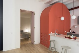 An arc-shaped, coral-colored volume that hides a powder room has become a main feature of the design.