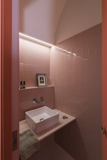 The guest bathroom sits hidden in a coral-colored volume off the kitchen.