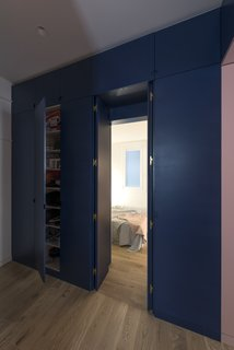 The lacquered panels of the bespoke storage unit conceal direct access to the bedroom from the main entrance through a double door.