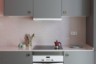 The kitchen cabinets are finished in a warm gray, and are fitted with vintage, brass concave handles. The countertops are a pink terrazzo-like quartz.