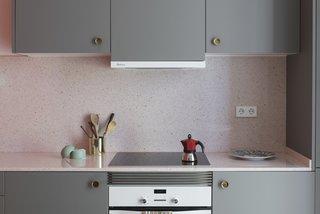The kitchen countertops are a pink terrazzo-like quartz.