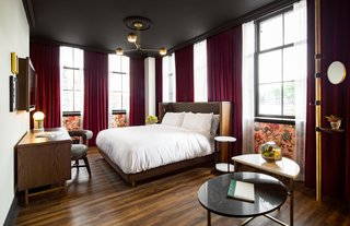 The dark velvet floor-to-ceiling curtains paired against the bronze lighting and wooden floors define the vintage vibe in the guest rooms.