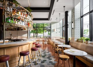 The cafe is designed with plush leather benches and marble tables around its perimeter, as well as black pendant lights hanging above. The flooring marks the separation between the cafe seating and the center bar.