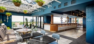 A glass volume was inserted on the roof to host the lounge and bar. Blue walls and brass pendant lighting in the area are juxtaposed against the bright and airy dining space.