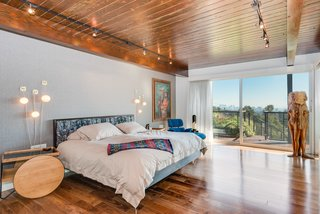 The master bedroom on the upper level features hardwood floors and redwood ceilings, and opens to a terrace.