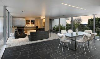 Bertram retained Neutra's open floor plan and minimalist aesthetic—soft white tones contrast with the dark slate geometric flooring.