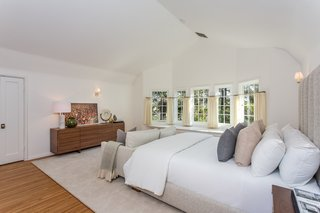 This bright bedroom has an ensuite bath and a wood-burning fireplace.