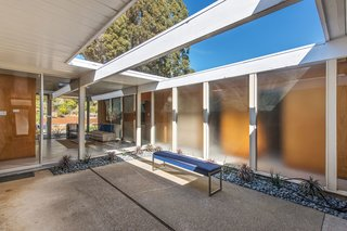 The front door opens to a central atrium, a signature feature of Eichler homes. Also true to form is the dwelling's floor-to-ceiling glass windows, which overlook the backyard. These help invite the outdoors in, while also allowing ample natural light to enter.