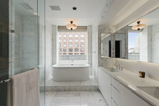 The master bath features Statuary marble, heated floors, a Kaldewei Vaio Duo oval freestanding tub, a frameless glass-enclosed shower, Lefroy Brooks fixtures, and a Valcucine vanity.
