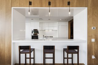 The Gwathmey Siegel–designed kitchen boasts Valcucine cabinetry of striated elm and smoked glass, Jet Mist granite, a Sub-Zero refrigerator, a Miele oven and dishwasher, a Gaggenau cooktop and fully vented hood, wine storage, and a cut-out breakfast bar that opens to the living room.
