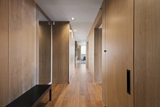 Wood-paneled walls concealing storage line the corridor and play off the unit's oak wood flooring.