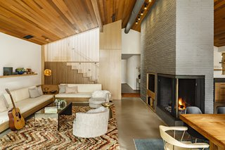While the redesign of the staircase is a contemporary touch, it could have easily existed in the home's original state. The wood slat screen blends with the wooden staircase and the wood ceiling, opening the space to make it feel bigger—a huge improvement over the sheetrock wall that had been previously there. The addition of Holly's custom-design for a built-in sofa also helps to keep the living room comfortable and cozy.